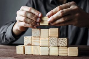 Businessman_building_a_pyramid_with_empty_wooden_cubes._Concept_of_business_hierarchy_and_business_strategy.