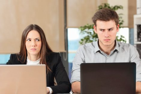 Front_view_of_two_angry_businesspeople_using_computers_disputing_at_workplace_and_looking_sideways_each_other_with_envy