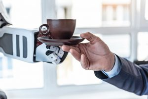 Coffee_is_fuel._Close_up_male_hand_is_taking_cup_of_delicious_espresso_from_robot_in_office