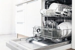 Open_dishwasher_with_clean_dishes_in_the_white_kitchen