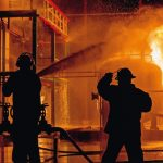 Firemen_using_water_from_hose_for_fire_fighting_at_firefight_training_of_insurance_group._Firefighter_wearing_a_fire_suit_for_safety_under_the_danger_case.