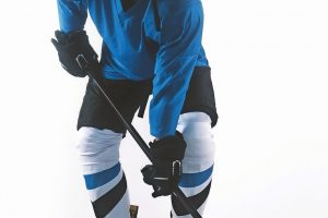 Portrait_of_Caucasian_male_ice_hockey_player_in_uniform_posing_against_white_background