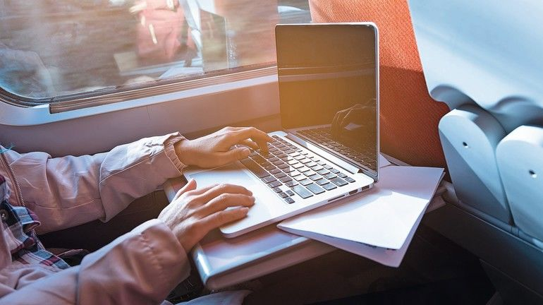 Close_up_of_young_woman_traveling_by_train_and_working_on_laptop._Business_travel_concept.