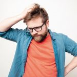 Young_bearded_man_with_glasses_is_in_doubt,_he_is_confused,_looks_down_thoughtfully_and_scratches_his_head._Isolated_on_a_white_background.