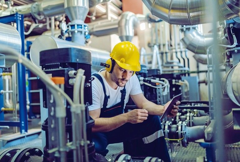 Focused_plant_worker_in_overalls,_with_protective_helmet_on_head_and_antiphons_on_ears_using_tablet_for_checking_machine_while_crouching.