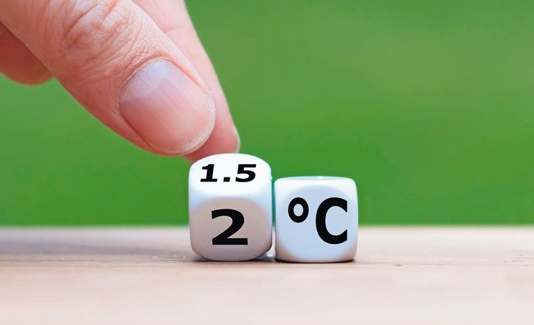 """Symbol_for_limiting_global_warming._Hand_turns_a_dice_and_changes_the_expression_""""2°C""""_to_""""1.5°C"""",_or_vice_versa."""