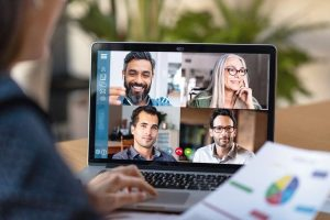 Back_view_of_business_woman_talking_to_her_colleagues_about_business_plan_in_video_conference._Multiethnic_business_team_using_laptop_for_a_online_meeting_in_video_call._Group_of_buinessmen_and_businesswomen_smart_working_from_home.