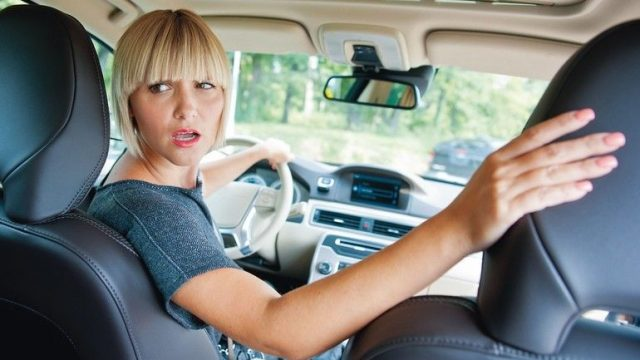 attractive_woman_driver_looking_back_and_parking_car