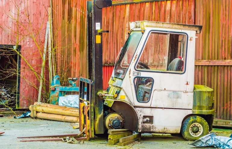 Old_abandoned_fork_lift_with_missing_wheel_and_supported_by_stack_of_wood._Green_moss_and_rust_has_taken_over.