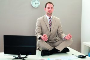 Businessman_Sitting_On_The_Desk_And_Meditating_With_Eyes_Closed