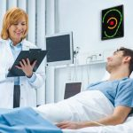 Friendly_Female_Doctor_Visits_Happy_Recovering_Man_who_is_Lying_in_Bed,_She_Asks_Him_Questions_and_Fills_Medical_Chart._Friendly_Doctor_and_Sick_Man_in_a_Clean_Hospital_Ward.