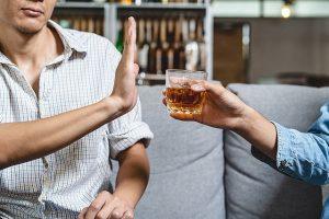 Ein Mann weist ein Glas mit Alkohol zurück