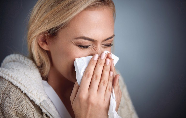 _Cold_woman_holding_handkerchieif_blowing_nose