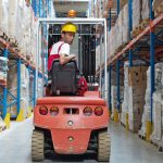 Young_man_sitting_on_a_fork_lift