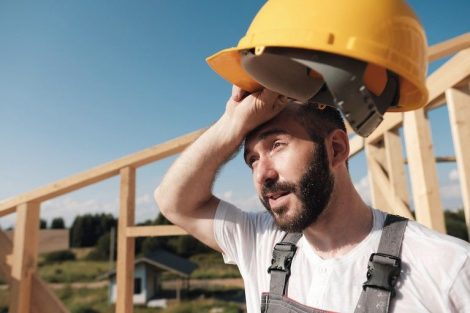 The_man_is_a_builder_on_the_background_of_the_roof_of_a_frame_house,_in_a_yellow_helmet_and_gray_overalls.