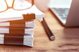 Stack_of_documents_placed_on_a_business_desk_in_a_business_office.