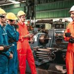 Skillful_worker_attending_brief_meeting_in_the_factory_._Industrial_people_and_manufacturing_labor_concept_.