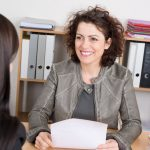 Businesswoman_conducting_a_job_interview_seated_at_her_desk_in_her_office_holding_a_folder_and_smiling_at_the_potential_female_candidate