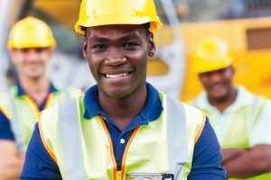 happy_african_american_construction_worker_in_front_of_colleagues