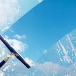 Rubber_squeegee_cleans_a_soaped_window_and_clears_a_stripe_of_blue_sky_with_clouds,_concept_for_tranparency_or_spring_cleaning,_copy_space_in_the_background