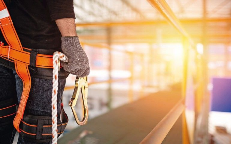 Construction_worker_wearing_safety_harness_and_safety_line_working_at_high_place