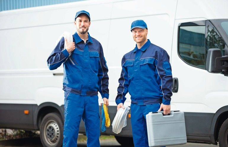 Smiling_Repairman_With_Toolbox_And_Cable_Standing_In_Front_Of_Vehicle