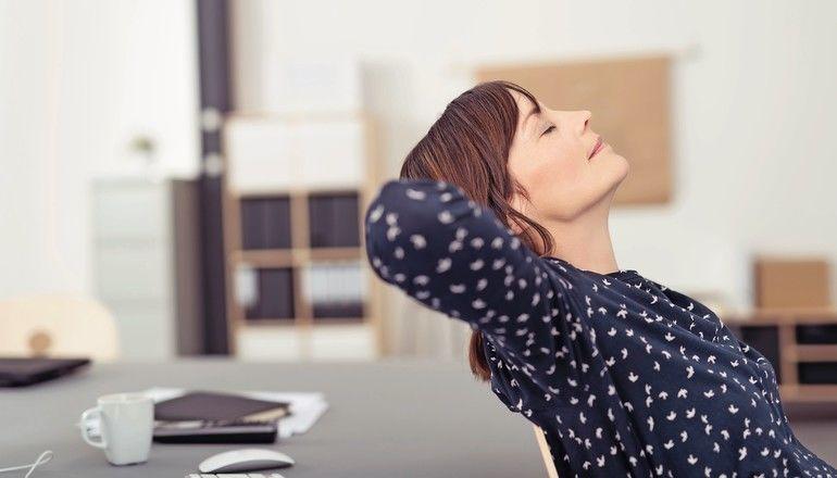 frau_im_büro_lehnt_sich_entspannt_zurück