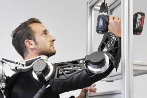 Ein Exoskelett am Arm hilft einem Beschäftigten, den Bohrer hochzuhalten.