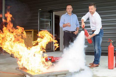 Zwei Männer üben den Umgang mit einem Feuerlöscher