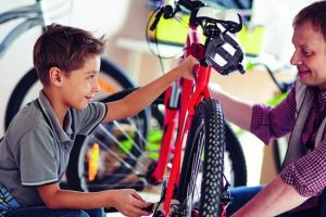 Father_helping_his_son_fix_a_bicycle