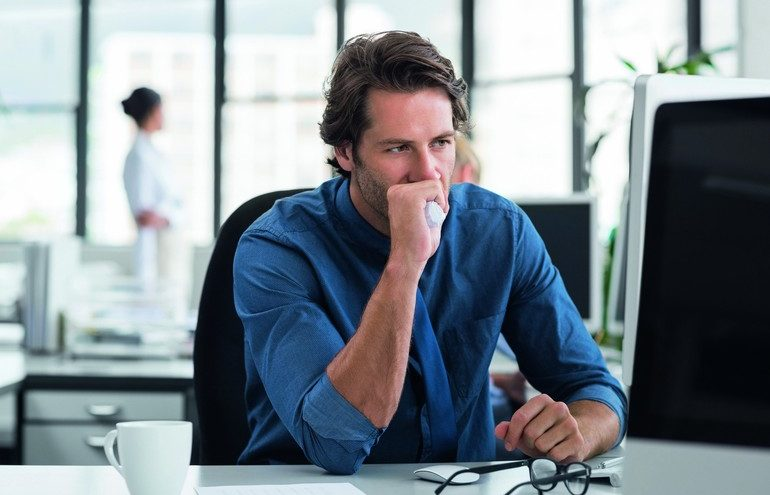 Tired_and_depressed_businessman_sitting_in_office_at_the_table._Tensed_businessman_with_hand_on_mouth_staring_at_computer_screen._Stressed_business_man_thinking_about_solution_while_looking_at_computer.
