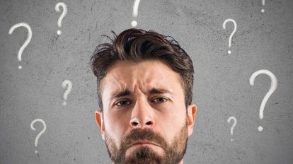 Confused_and_pensive_businessman_worried_about_the_future,_surrounded_by_question_marks