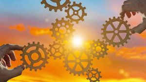 Hands_collect_gear_in_a_puzzle_against_the_sky_in_the_sunset._Business_concept_idea,_partnership,_innovation,_teamwork,_cooperation
