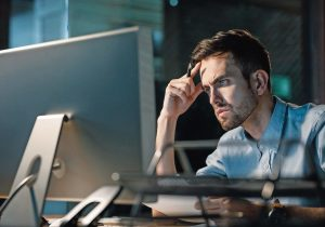 Man_focusing_on_information_in_computer_working_alone_late_at_night_in_modern_office._