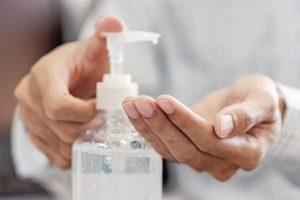 Man_hands_using_wash_hand_alcohol_gel_or_sanitizer_bottle_dispenser,_against_Novel_coronavirus_or_Corona_Virus_Disease_(Covid-19)_._Antiseptic,_Hygiene_and_Health_concept