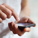 man_hands_touching_smartphone_bright_background,_closeup