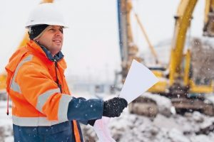 Civil_engineer_at_construction_site_is_inspecting_ongoing_works_according_to_design_drawings_in_difficult_winter_conditions