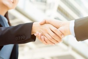 Businesswoman_making_handshake_with_a_businessman,_female_leader_concept_-_panoramic_web_banner
