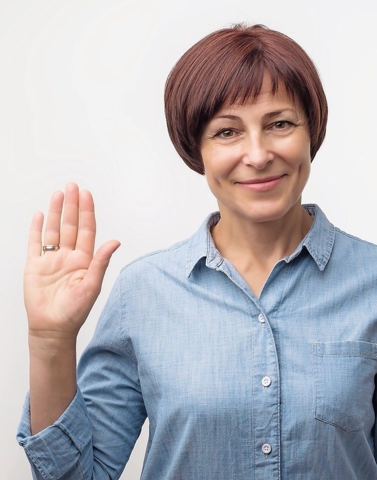 Positive_mature_caucasian_woman_smiling_friendly_and_waving_hand_at_camera._Business_and_welcome_concept.