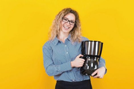 Portrait_of_attractive_curly-haired_woman_in_striped_shirt_and_eyeglasses_isolated_on_orange_background_holding_coffee_machine_advertising_concept.