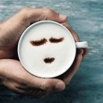 high-angle_shot_of_a_young_caucasian_man_holding_a_cup_of_cappuccino_with_a_happy_face_drawn_with_cocoa_powder_on_the_milk_foam,_on_a_gray_rustic_table