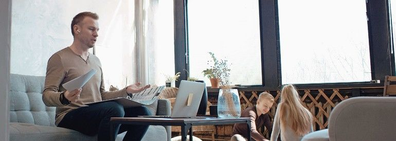 Mid_30s_Caucasian_male_working_from_home,_having_a_video_call_with_colleagues._Family_playing_in_the_background._Stay_home,_quarantine_remote_work