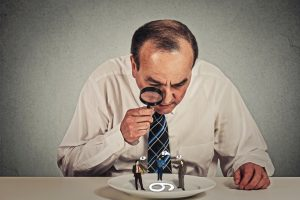 Curious_corporate_businessman_skeptically_meeting_looking_at_small_employee_standing_on_table_plate_through_magnifying_glass_isolated_grey_wall_background._Human_face_expression,_attitude,_perception