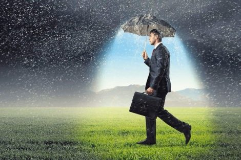 Young_businessman_with_umbrella_under_rain_walking_on_field