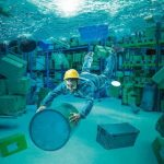 Worker_clings_to_a_bin_in_a_totally_flooded_warehouse._Abstract_underwater_image,_concept_of_problems_at_work.