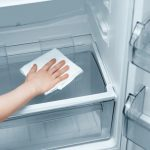 The_girl's_hand_with_a_white_rag_washes_the_refrigerator