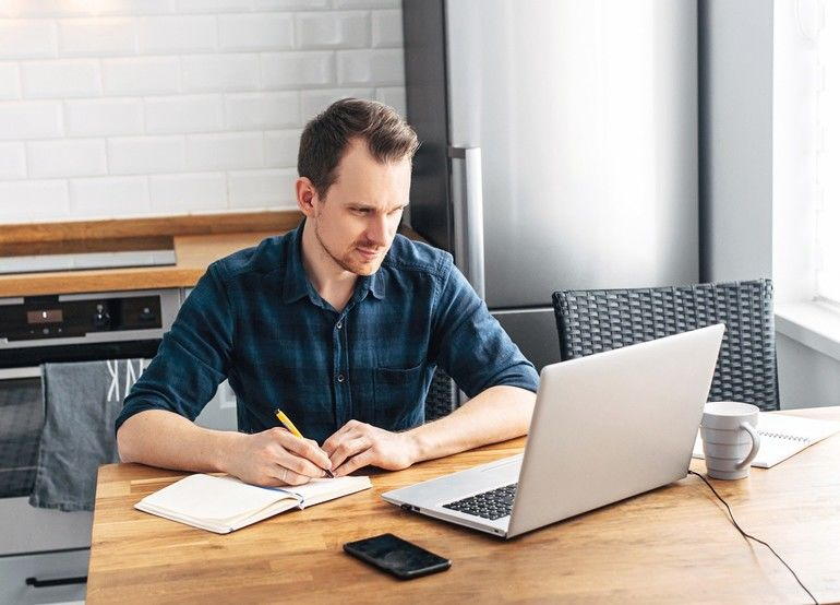 Home_office,_distant_work,_freelancer._A_young_man_in_a_casual_shirt_in_the_kitchen_at_home_uses_a_laptop._He_writes_the_information_with_a_pen_in_a_notebook.