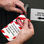 electrician_placing_a_lock_out_tag_out_tag_on_electrical_equipment