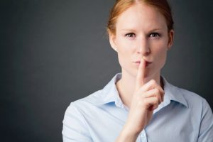 Young_businesswoman_gestures_for_silence_or_keeping_a_secret_with_one_finger_before_her_lips.
