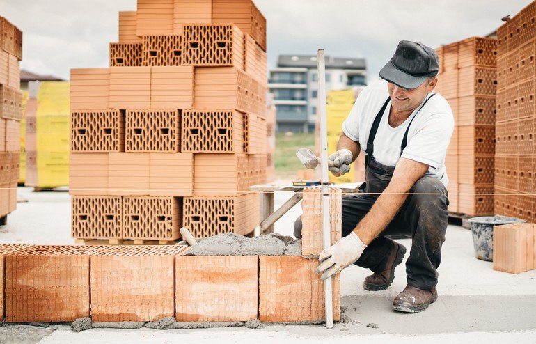 construction_worker_building_walls_and_working_with_bricks_on_construction_site